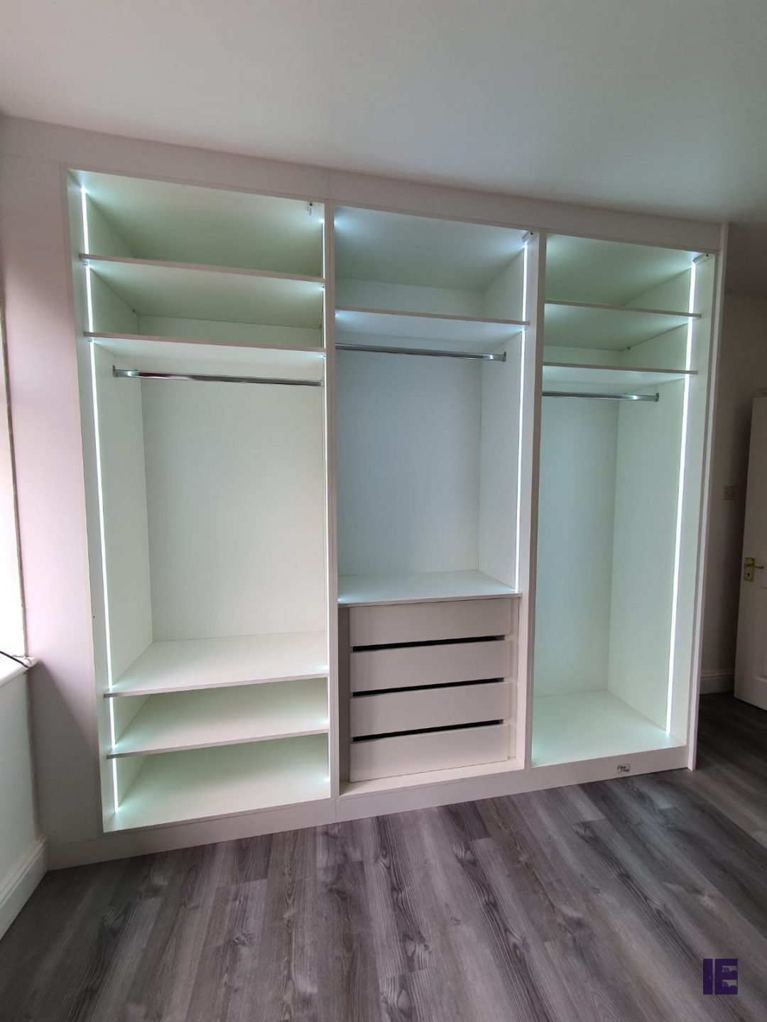 bespoke fitted HInged wardrobes in matt white finish with LED
