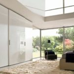 Living Room With High Gloss Sliding Door Fitted Wardrobe and Frameless Top Hung in White Gloss and Matt